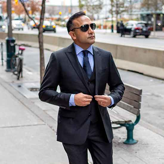Rocky Badhwar buttoning up suit with sunglasses on