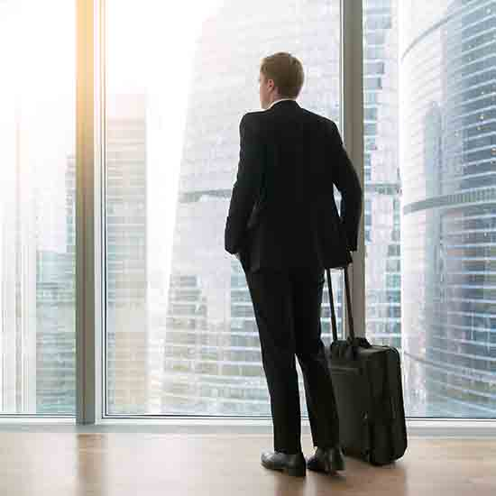 business man with a suitcase looking out a condo window